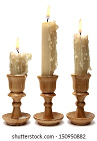 three burning candles in wooden candlesticks isolated on a white background.