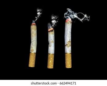 Three burning cigarettes on black background.