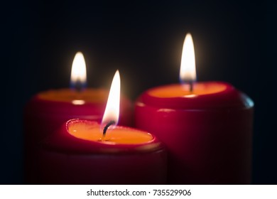 Three burning red Christmas candles on a black background closeup