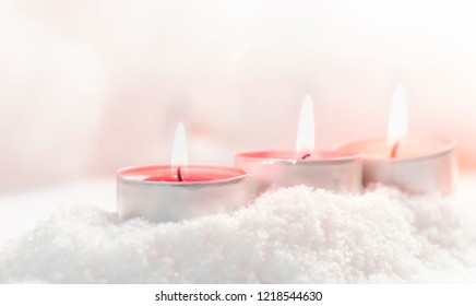Three burning tealights in the snow