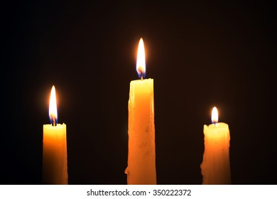 Three burning wax candles on a black background. religion