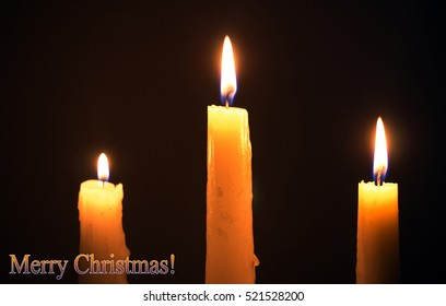 Three burning wax candles on a black background. Christmas