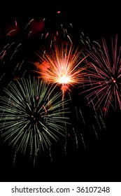 Three bursts of fireworks, one white-hot, with a few puffs of smoke and many falling embers from another