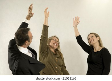 Three business associates smiling with their hands in the air. Horizontally framed photo.