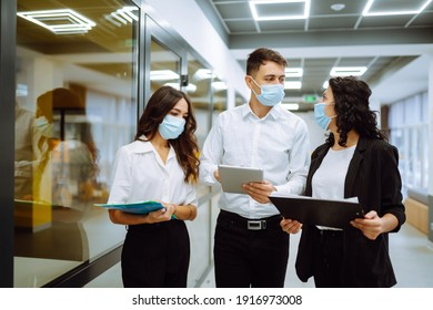 Three business colleagues in protective face mask discussing work related matters on an office building hallway. Teamwork during pandemic in quarantine city. Covid-19.