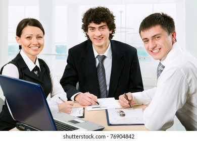 Three business colleagues sitting around table and working together, looking at camera