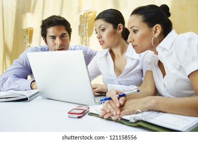 Three business colleagues using laptop in office