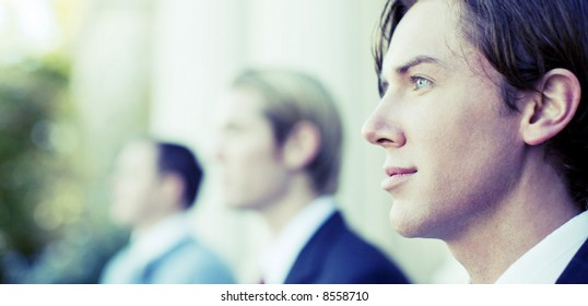 three business men standing and looking in same direction