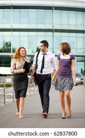 Three business partners walking along the office building. Happy people speaking about their job, career and new ideas for the future business projects.
