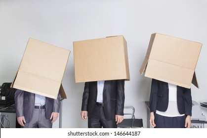 Three business people with boxes over their heads in an office