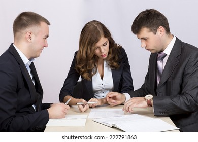 Three business people discuss the deal. They sit around the table and pointing the peace of paper with contract printed on it.