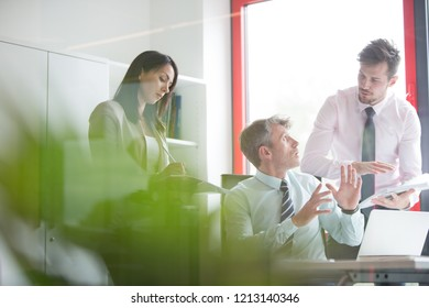 Three business people having a serious meeting with secretary taking notes