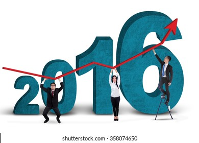 Three business people holding upward arrow together with numbers 2016, isolated on white background