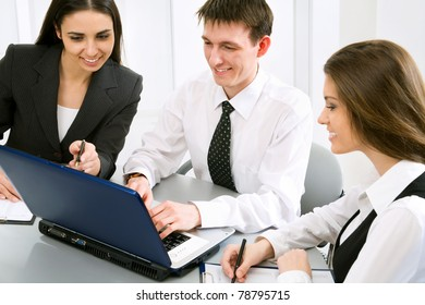 Three business people at the office with a laptop