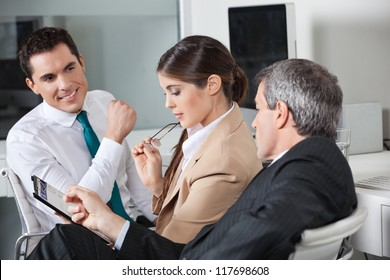 Three business people planning a capital investment in the office
