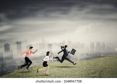 Three business people running speed on the hill to compete together with cloudy city background