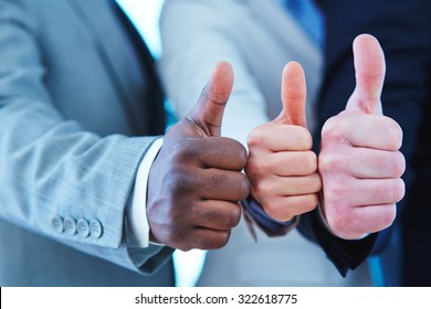 Three business people showing thumb up gesture