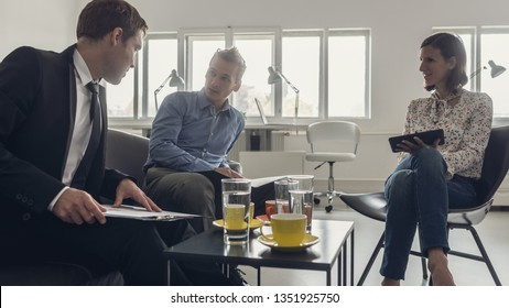 Three business people sitting around a coffee table in an office having a meeting.