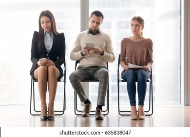Three business people sitting in line in waiting room for a long time, amusing themselves, meeting start delay, someone is late, getting bored, candidates await in queue for job interview