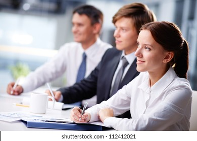 Three business people sitting at seminar, the focus is on woman