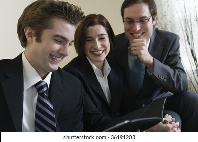 Three business people smiling.