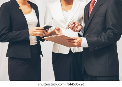 three business people standing and discussing their work