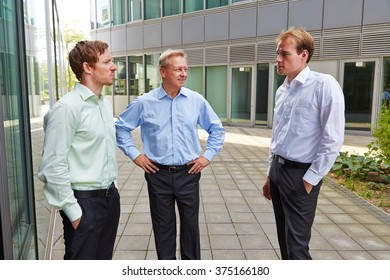 Three business people standing outside and talking during lunch break