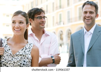 Three business people standing together next to a classic office building in the city on a sunny day, smiling and laughing.