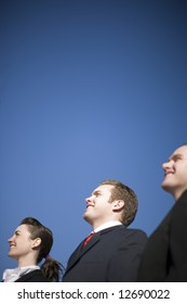 Three business people in suits standing in a row smiling and looking in the same direction with a blue sky background