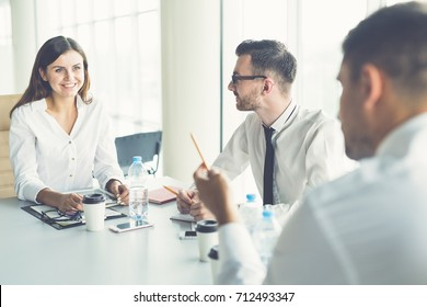 The three business people talk at the table