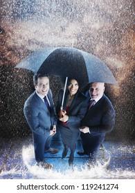 Three business people under one umbrella during rainy season