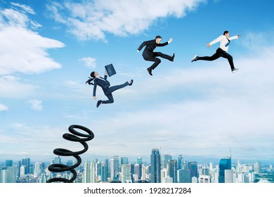 Three business people using a springboard to jumping above modern city with blue sky background