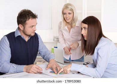 Three business people working and discussing at office.