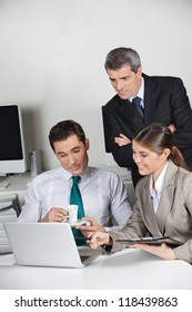 Three business people working together at laptop computer in the office