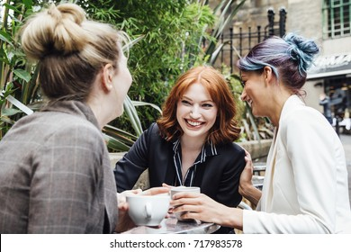 Three business women are enjoying a coffee break together in the city. They are sitting in the outdoor area of a cafe and are all laughing and talking together,