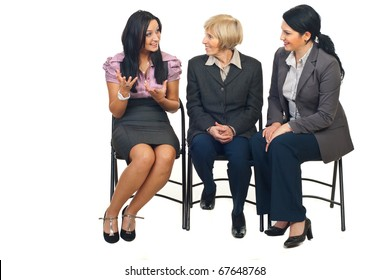 Three business women having a happy discussion at conference and sitting on chairs isolated on white background