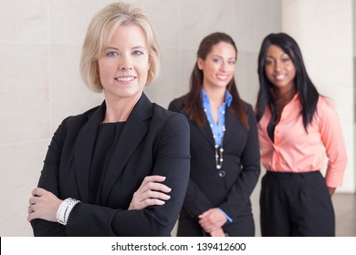 Three business women of varying ethnicities in suits, standing together, smiling and looking at camera, in office