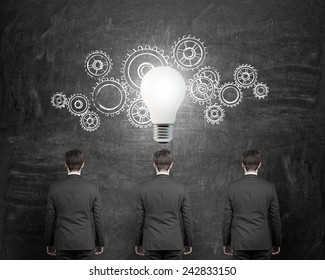 three businessman with gears and bulb over head