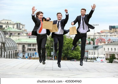 Three businessman jumping with paper bags in her hand on the background of the city
