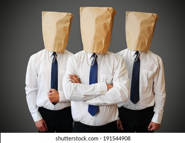 Three businessman with a paper bag on head