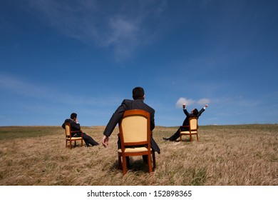 three businessman sitting in a chair in outdoor looking to the field