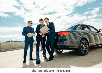three Businessman Using Digital Tablet Outside against car.