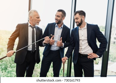 Three businessmen in black business suits are posing in the office. Two of them hold golf clubs in their hands. They have fun communicating