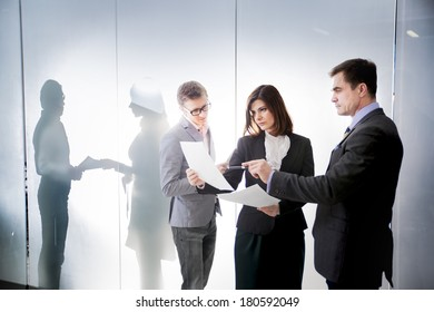 Three businessmen communicate on the background of the office and the people behind the glass