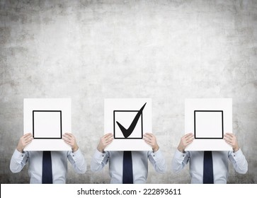Three businessmen are holding a check boxes, a concept of decision making process.