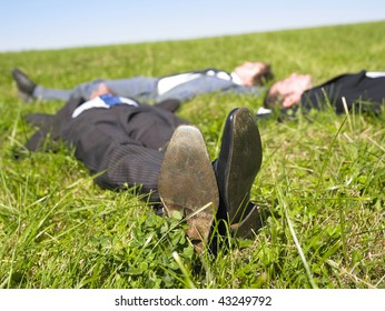 Three businessmen lying in the grass. Horizontal.