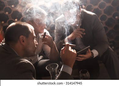 Three businessmen sitting in the wine cellar drinking wine and smoke cigar, resting after a hard day at work.