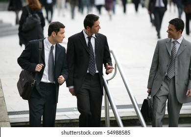 Three businessmen in suit coming down stairs
