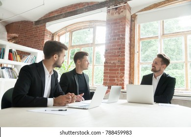Three businessmen in suits negotiating discussing business sitting at conference office table at meeting, board of directors planning new project, partners brainstorming talking about work results