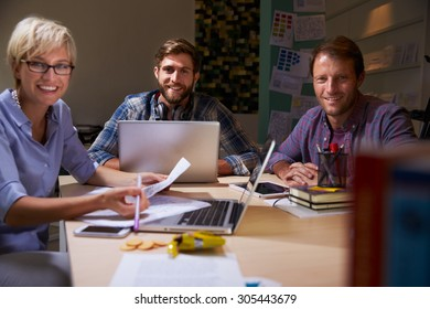 Three Businesspeople Having Late Meeting In Office